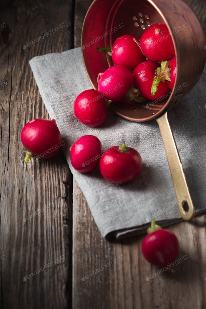 Rote Radieschen in einem Sieb auf einem Holztisch