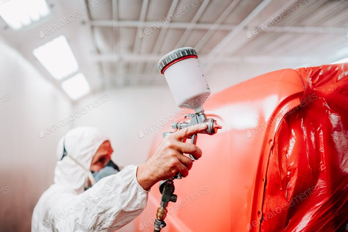 Close-up of spray gun and airbrush painting a red car. details of automotive manufacturing
