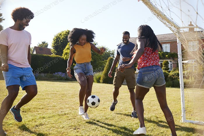 Two black adult couples playing football in garden