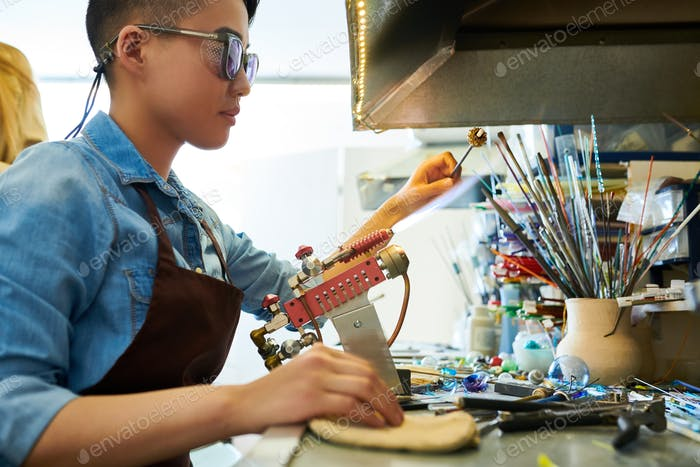Asian Artist Shaping Glass in Flame