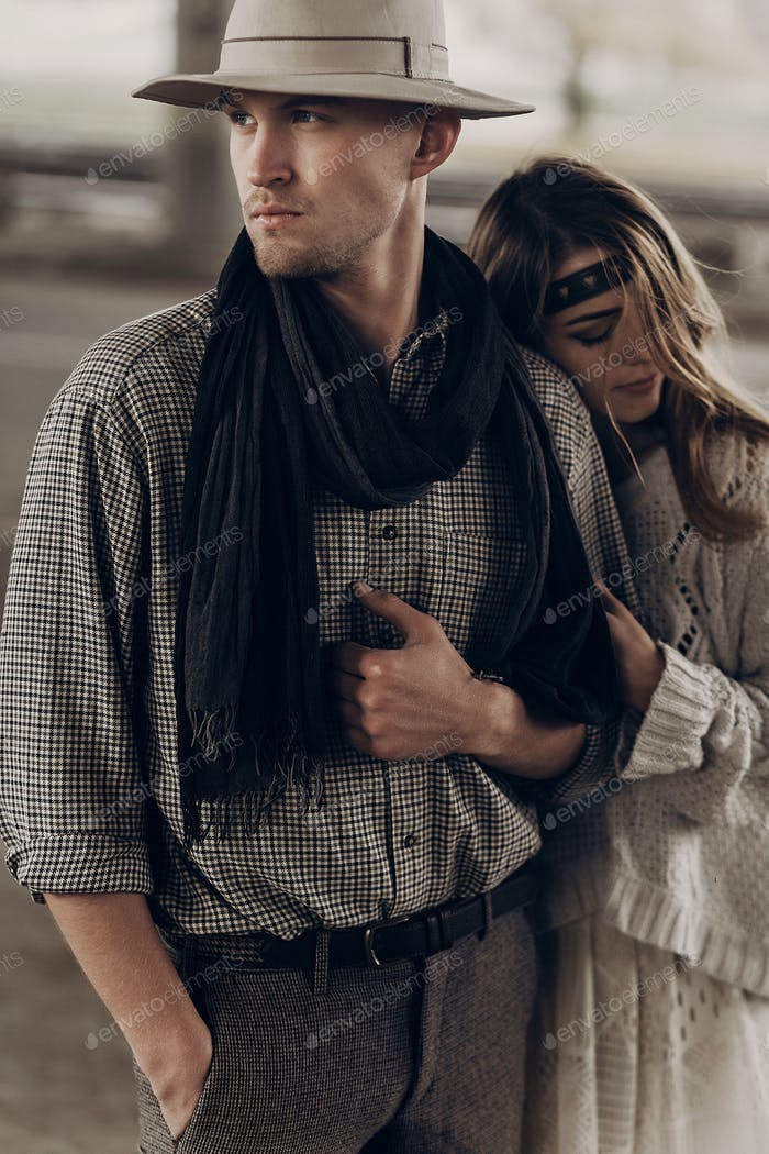 Handsome cowboy  man with hat being hugged by beautiful indie woman