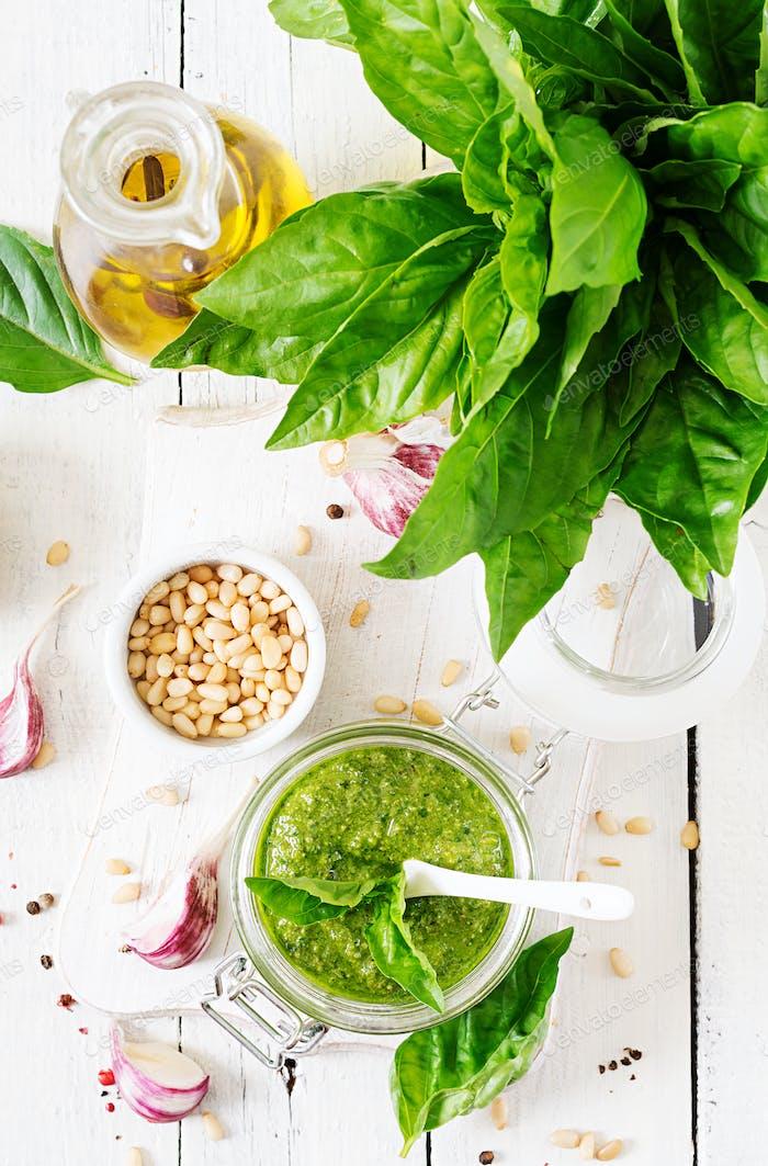 Homemade pesto sauce fresh basil, pine nuts and garlic on white wooden background.