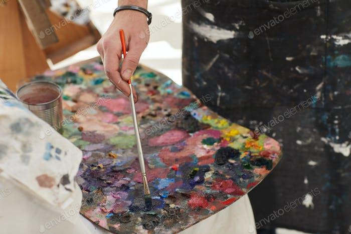 Unrecognizable Man Mixing Paint on Palette