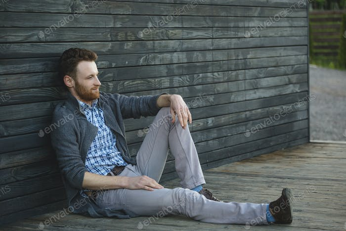 Handsome young man sitting on the wooden floor