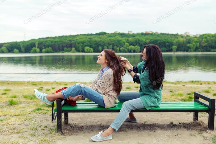 Two beautiful girls relaxing while making hairdo enjoying time together