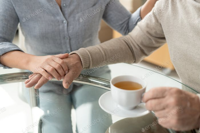 Careful young daughter holding hand of her retired aged father having cup of tea