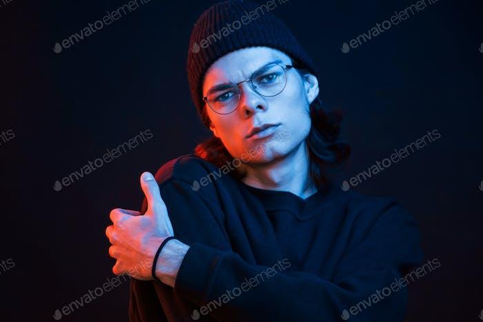Calm and quiet. Studio shot in dark studio with neon light. Portrait of serious man