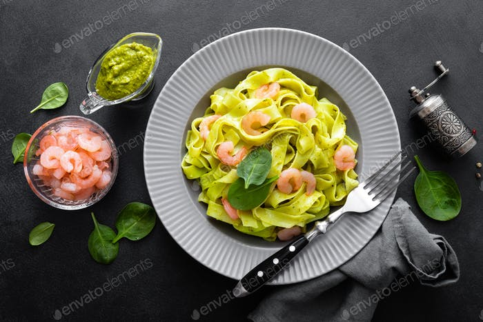 Boiled fettuccine pasta with fresh spinach pesto and shrimps on black background. Italian cuisine