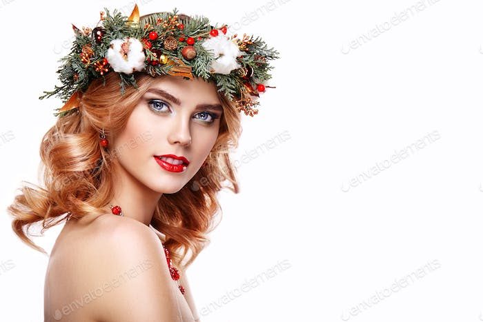 Portrait of beautiful young woman with Christmas wreath