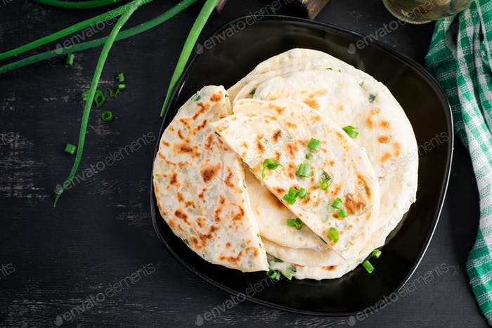 Traditional indian bread. Pita bread with green onions. Onion naan. Top view