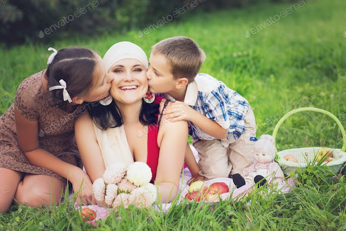 mother with kids having picnic outdoors