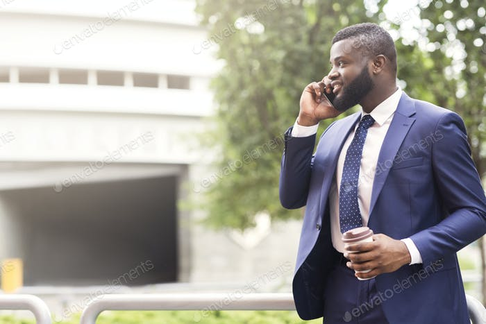Bearded African American businessman talking on cell phone with customer
