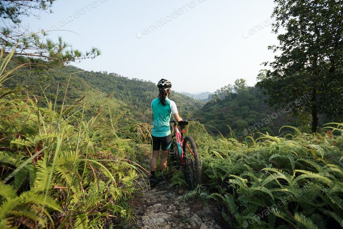 Woman mountain biker looking at the view on mountain top