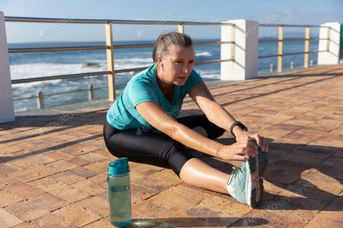 Female jogger stretching on seaside