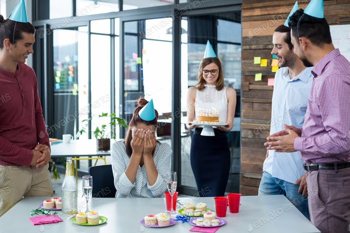 Businesspeople giving surprise birthday party to colleague