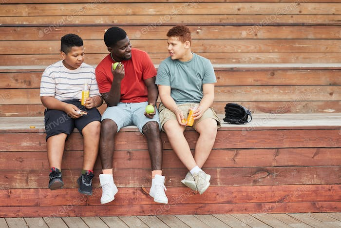 Father Sitting With Sons On Bleacher Bench
