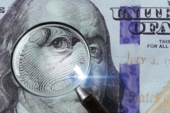 100 US Dollar under magnifying glass