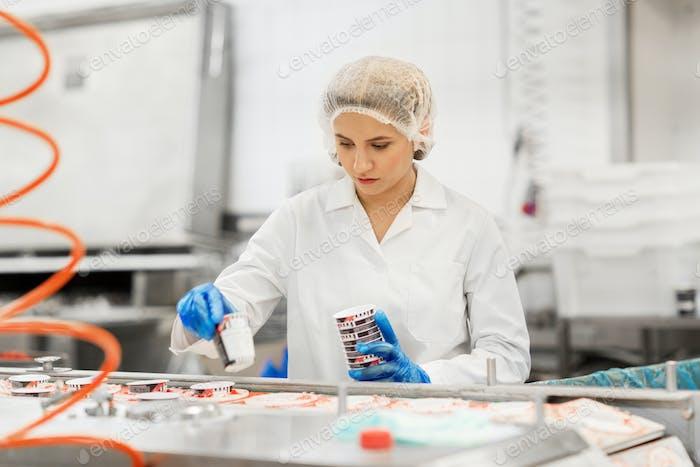 Frau arbeitet an der Eisfabrik Förderband