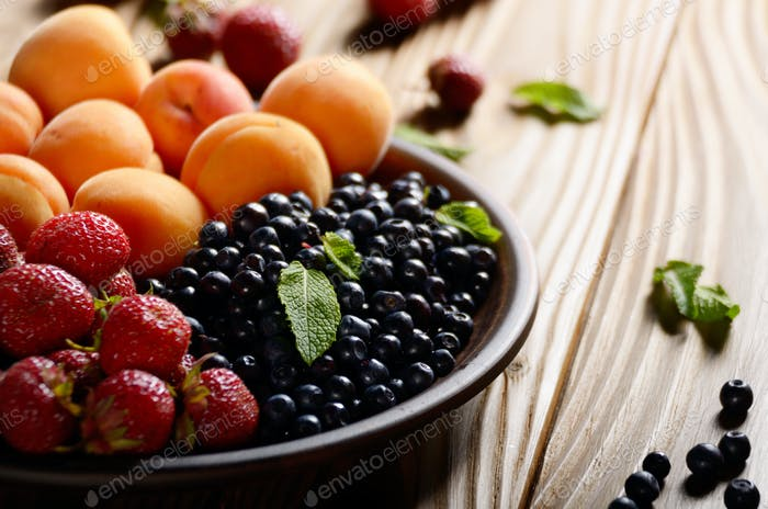 Ripe organic blueberries apricots and strawberries in clay plate