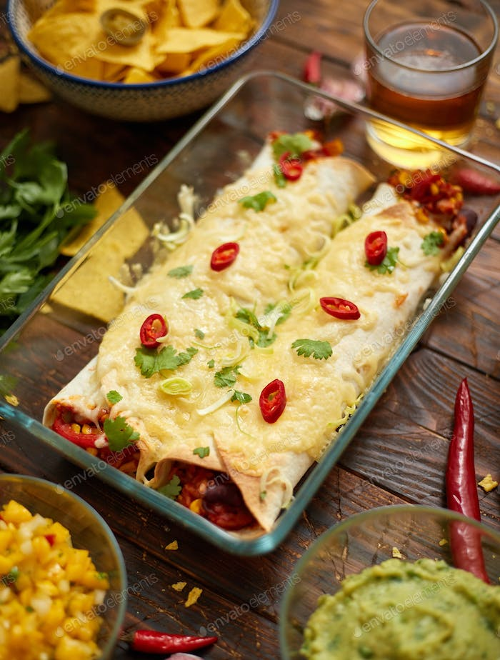 Vegetable Burritos served in glass heatproof dish. With salsa, guacamole, nachos and ingredients