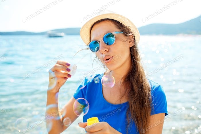 Happy young girl blowing soap bubbles on the seashore