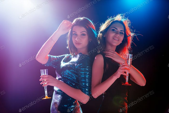 Two beautiful girls dancing at the party drinking champagne