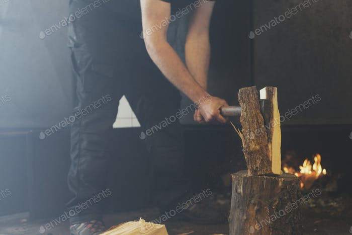 Mid section of man splitting log in half with ax