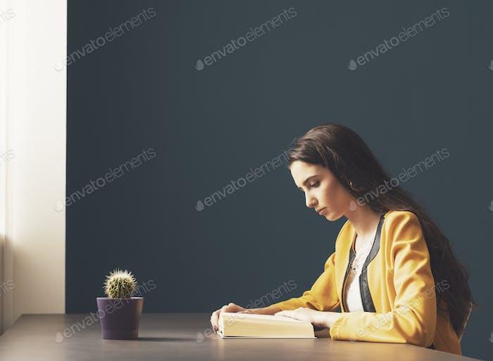 Junge Frau liest ein Buch zu Hause
