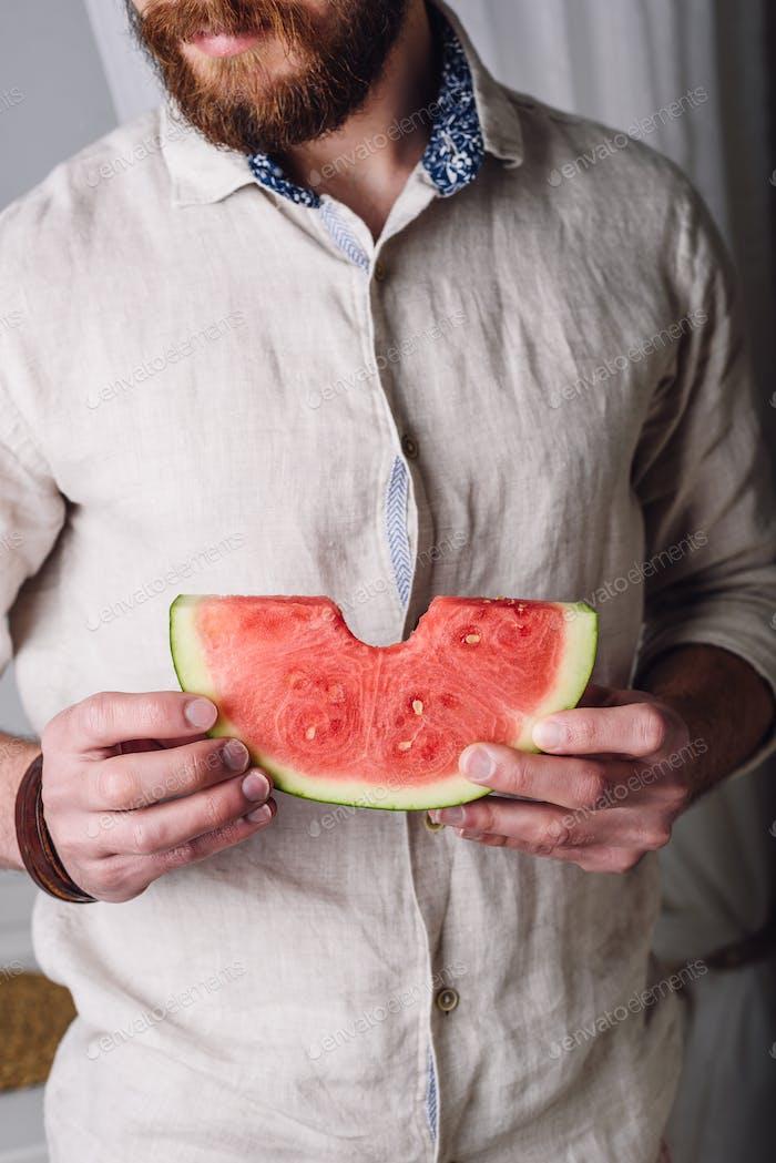 Bärtiger Mann im Hemd mit gebissenem Stück Wassermelone