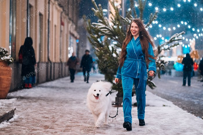 Woman walking down with white dog by alley
