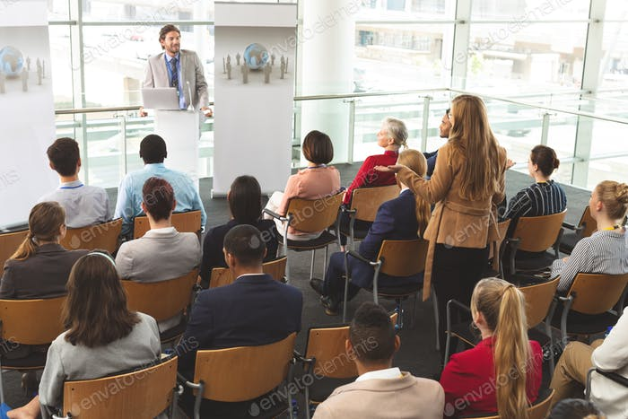 Businesswoman interacting with businessman speaking at business seminar in modern office building