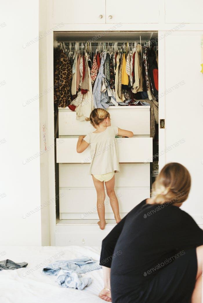 Chica joven en busca de ropa en una cómoda, su madre sentada en una cama, mirando.