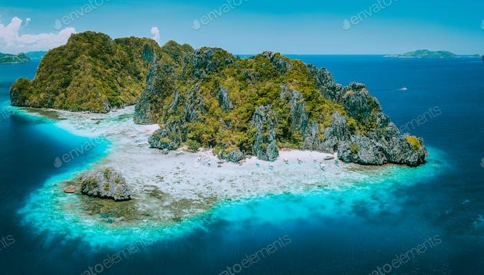 Aerial drone view of tropical Shimizu Island and pristine beach in blue ocean El Nido, Palawan