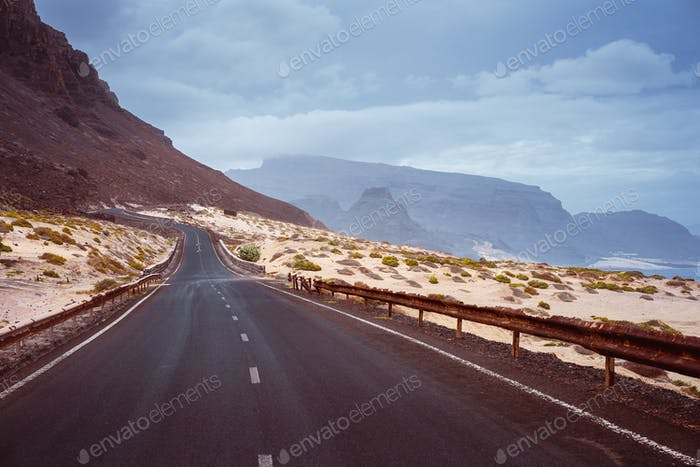 Asphalt road leads between black volcano erosion mountain and white sand dunes. Breathtaking