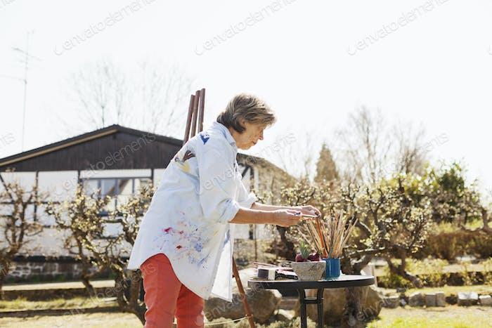 Seitenansicht der Seniorin Malerin, die außerhalb des Kunststudios arbeitet