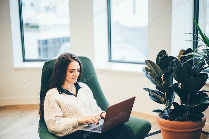 Бизнесвумен работает над ноутбуком в современном коворкинге.