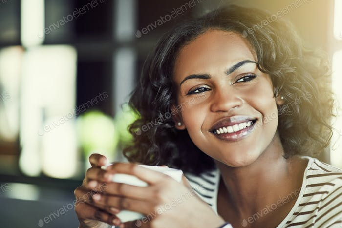 Smiling young African woman enjoying fresh coffee in a cafe