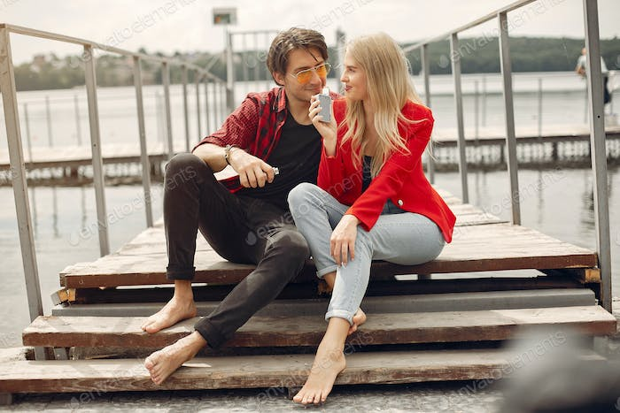 Stylish young couple with vape in a city