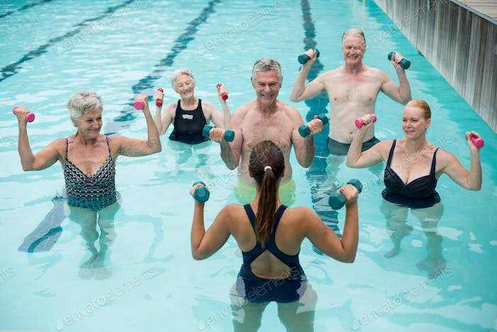 Trainer and senior swimmers exercising in swimming pool