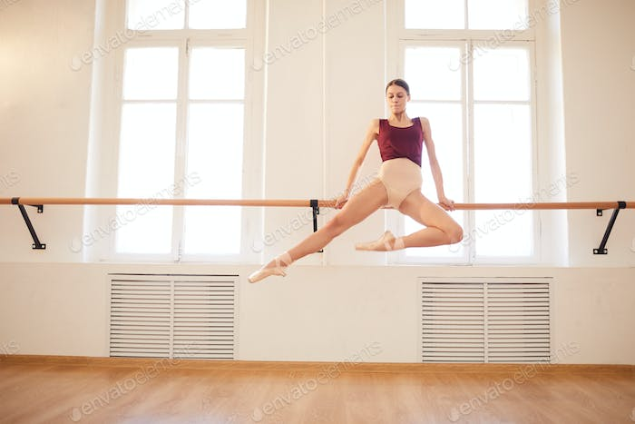 Ballerina doing elegant pull-up on barre