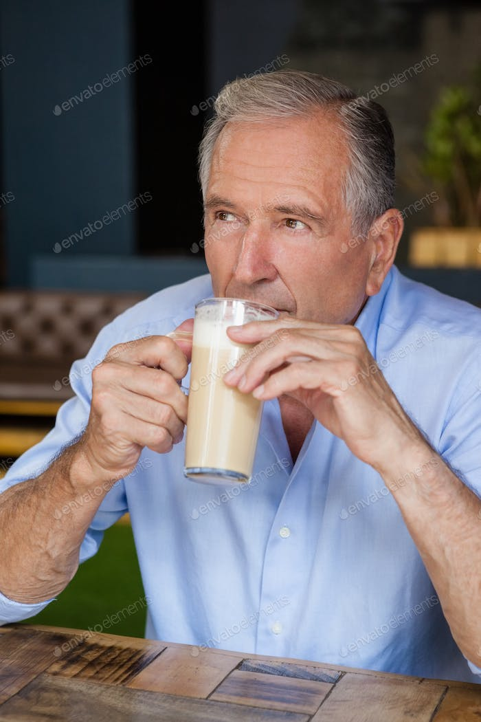 Senior thoughtful man holding cold coffee while sitting at table