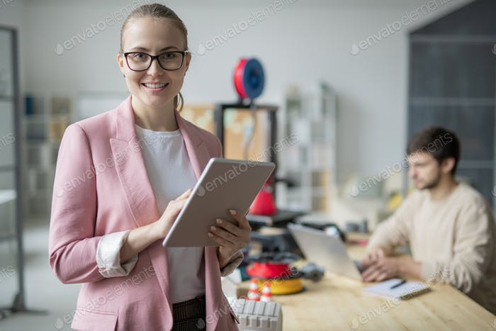 Young smiling businesswoman with touchpad on background of colleague by desk