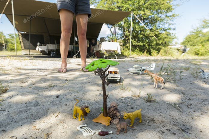 Eine Safari-Szene auf dem Sand, Spielzeug-Jeeps und Safari-Tiere auf dem Boden und die Beine eines Zuschauer.