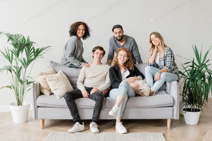 Joyful intercultural teenagers in casualwear relaxing on sofa together