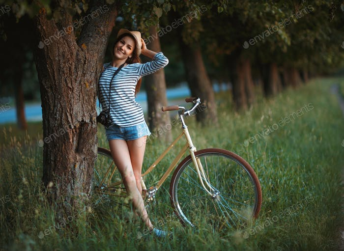 Lovely young woman in a hat with a bicycle in a park