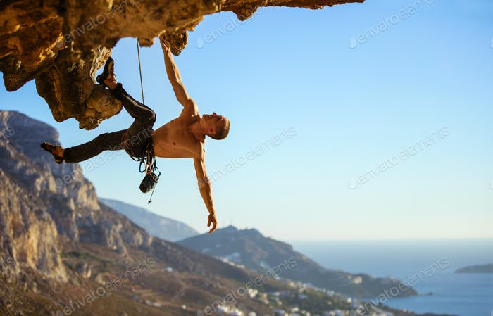 Young man struggling to climb ledge on cliff