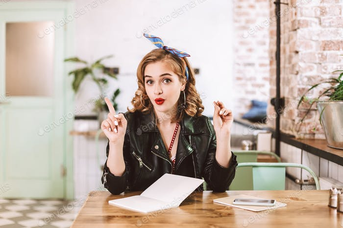 Pinup girl at cafe with notebook and pencil and looking in camera showing idea gesture