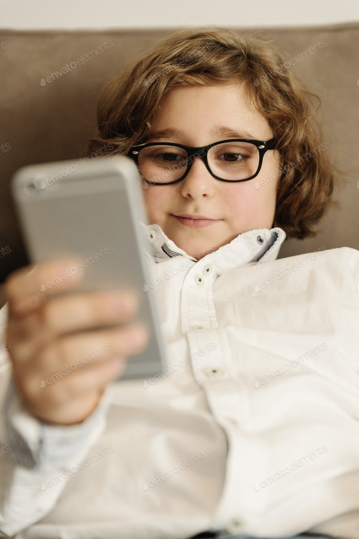 Child boy using his mobile phone.