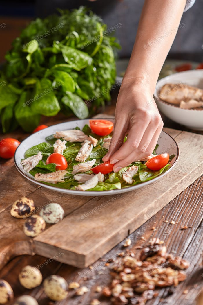 Woman's hand puts a piece of tomato in a plate with spinach and meat on a wooden table. Salad