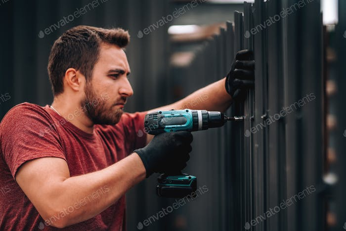 Portrait of construction worker installing metal elements using cordless screwdriver